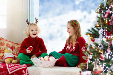 Photo pour Child decorating Christmas tree at home. Little boy and girl in knitted sweater with handmade Xmas ornament. Family celebrating winter holidays. Kids decorate living room and window for Christmas. - image libre de droit