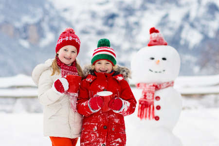 Photo pour Child building snowman. Kids build snow man. Boy and girl playing outdoors on snowy winter day. Outdoor family fun on Christmas vacation in the mountains. Children play in Swiss mountain landscape. - image libre de droit