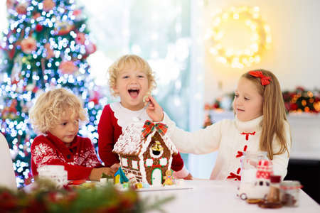 Photo pour Kids baking Christmas gingerbread house. Children celebrating winter holiday at home. Decorated living room with fireplace and tree. Family activity. Little girl and boy making cookies. - image libre de droit