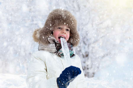 Photo pour Child playing with snow in winter. Little boy in warm jacket and knitted hat catching snowflakes in winter park on Christmas. Kids play in snowy forest. Cold weather outdoor fun for children. - image libre de droit