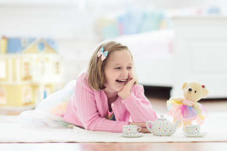 Photo pour Little girl playing with doll house in white sunny bedroom. Kid with toys. Role game for young children. Child with teddy bear toy. Kids play tea party with stuffed animals and dolls. Nursery interior - image libre de droit