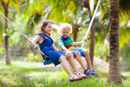 Foto de Kids on swing. Children swinging on playground in tropical resort with coconut palm trees. Summer beach fun. Family vacation in Asia. Boy and girl playing outdoor. - Imagen libre de derechos
