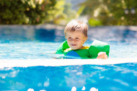 Photo pour Kids play in outdoor swimming pool of tropical resort. Swim aid for young child. Baby learning to dive. Group of children playing in water. Colorful life jacket. Beach and summer fun. - image libre de droit
