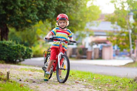 Foto de Kids on bike in park. Children going to school wearing safe bicycle helmets. Little boy biking on sunny summer day. Active healthy outdoor sport for young child. Fun activity for kid - Imagen libre de derechos