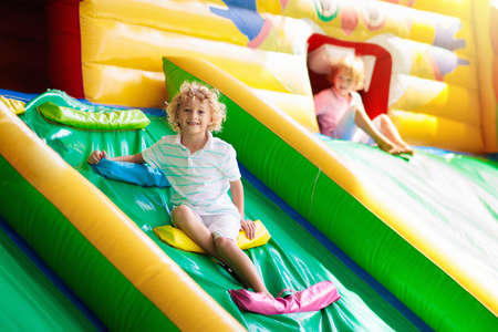 Photo pour Child jumping on colorful playground trampoline. Kids jump in inflatable bounce castle on kindergarten birthday party Activity and play center for young child. Little boy playing outdoors in summer. - image libre de droit