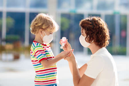Photo pour Family with kids in face mask in shopping mall or airport. Mother and child wear facemask during coronavirus and flu outbreak. Virus and illness protection, hand sanitizer in public crowded place. - image libre de droit