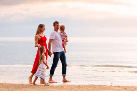 Photo pour Happy family with kids on tropical beach. Sea vacation. Parents and children walking at ocean shore at sunset. Summer fun. Travel with baby and young child. Mother, father, son and daughter playing. - image libre de droit