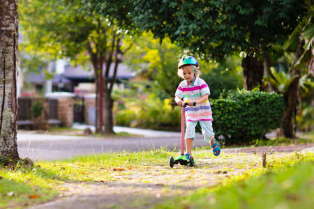 Photo pour Little boy riding scooter. Kids ride kick board. Child playing on suburban street on sunny summer day. Safe helmet for children. Healthy outdoor activity. Cute kid on his way to school. - image libre de droit
