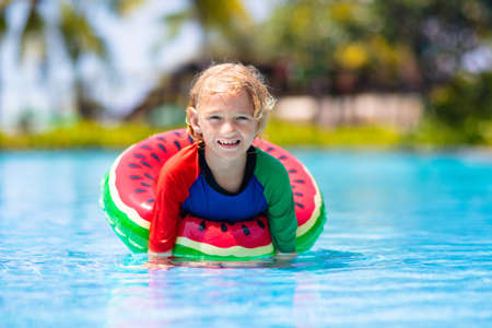 Photo pour Child in swimming pool floating on toy ring. Kids swim. Colorful rainbow float for young kids. Little boy having fun on family summer vacation in tropical resort. Beach and water toys. Sun protection. - image libre de droit