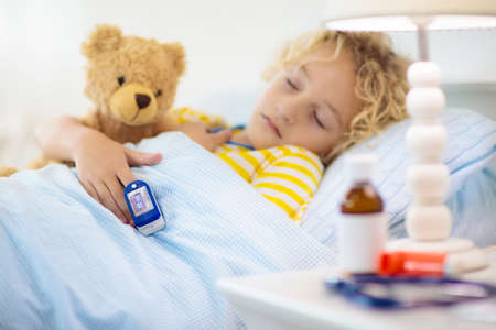 Photo pour Sick little boy with pulse oximeter on his finger. Asthma treatment. Ill child lying in bed. Unwell kid with chamber inhaler, cough medicine. Flu season. Bedroom or hospital room for young patient. - image libre de droit