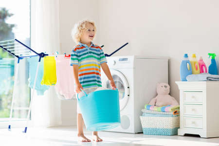 Photo pour Child in laundry room with washing machine or tumble dryer. Kid helping with family chores. Modern household devices and washing detergent in white sunny home. Clean washed clothes on drying rack. - image libre de droit