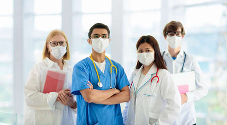 Foto de International doctor team. Hospital medical staff. Mixed race Asian and Caucasian doctor and nurse meeting. Clinic personnel wearing face mask and stethoscope. Coronavirus outbreak. - Imagen libre de derechos