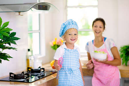 Photo for Mother and kid cook in white kitchen. Mom and child cooking at home. Little boy in chef hat and apron and mom cut vegetables for salad. Healthy nutrition for young children. Kids help prepare dinner. - Royalty Free Image