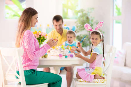 Photo pour Mother, father and kids color Easter eggs. Mom, dad, little girl and boy with bunny ears dying and painting for Easter egg hunt. Family and child celebration. Home decoration for spring holiday. - image libre de droit