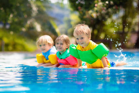 Photo for Kids play in outdoor swimming pool of tropical resort. Swim aid for young child. Baby learning to dive. Group of children playing in water. Colorful life jacket. Beach and summer fun. - Royalty Free Image