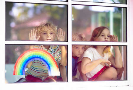 Photo for Coronavirus quarantine. Stay home. Kids sitting at window. Children drawing rainbow sign of hope. Boy and girl during corona virus lockdown. Child and pet. Family isolation indoors. Disease prevention - Royalty Free Image