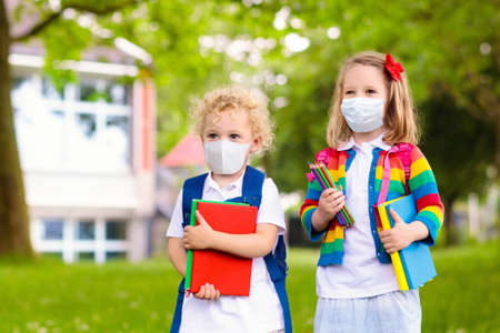 Photo pour School child wearing face mask during corona virus and flu outbreak. Boy and girl going back to school after covid-19 quarantine and lockdown. Group of kids in masks for coronavirus prevention. - image libre de droit