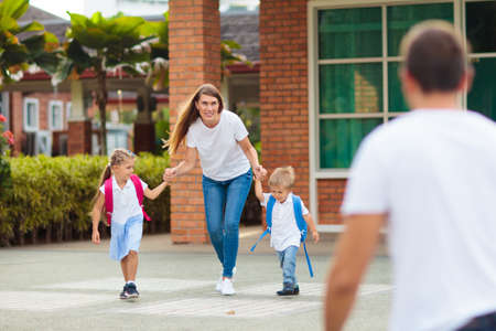 Mother and kids after school. Young mom picking up children after lessons in kindergarten or preschool. Pick up students. Boy and girl running to parents in school yard.