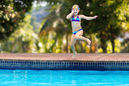 Photo pour Child jumping into water in swimming pool. Kids swim and play on family summer vacation in tropical resort. Little girl diving. Travel with young children. Healthy outdoor activity. Beach fun. - image libre de droit