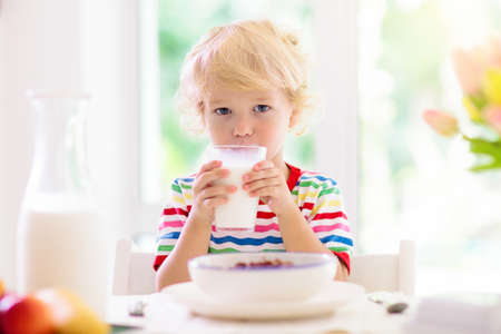 Foto für Child having breakfast. Kid drinking milk and eating cereal with fruit. Little boy at white dining table in kitchen at window. Kids eat on sunny morning. Healthy balanced nutrition for young kids. - Lizenzfreies Bild