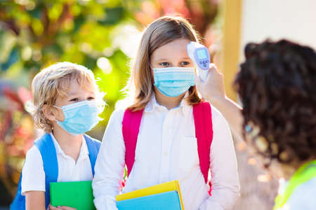 Foto de Temperature screening and medical check at school. Child in face mask in class in covid-19 outbreak. Teacher with thermometer at preschool entrance. Social distancing. Coronavirus prevention. - Imagen libre de derechos