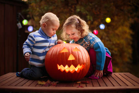 Photo pour Child carving Halloween pumpkin. Kids carve pumpkins for trick or treat jack o lantern. Autumn activity for children. Little girl in scary witch costume and hat. Kid playing in autumn garden. - image libre de droit