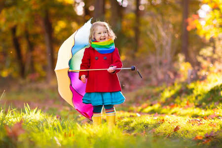 Photo pour Kid playing out in the rain. Children with umbrella and rain boots play outdoors in heavy autumn rain. Little girl jumping in muddy puddle. Kids fun by rainy fall weather. Child running in storm. - image libre de droit