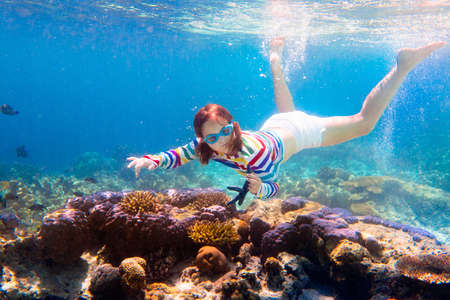 Photo pour Child snorkeling. Kids swim underwater. Beach and sea summer vacation with children. Little girl watching coral reef fish. Marine life on exotic island. Kid swimming and diving with snorkel and mask. - image libre de droit