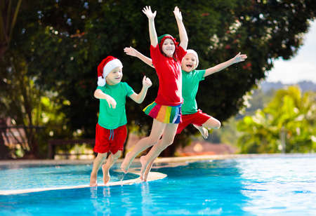 Photo pour Christmas vacation on tropical island. Kids in Santa hat playing in swimming pool on family Xmas vacation. Winter holidays at the beach. Travel with children. Boy and girl swim. Merry Christmas card. - image libre de droit