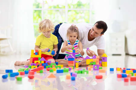 Photo pour Father and kids play with colorful blocks. Dad, little boy and girl build tower at home or day care. Educational toy for young child. Construction creative game for baby or toddler kid. - image libre de droit