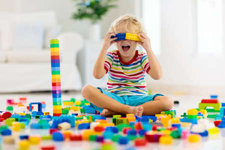 Photo pour Child playing with colorful toy blocks. Little boy building tower at home or day care. Educational toys for young children. Construction block for baby or toddler kid. Mess in kindergarten play room. - image libre de droit