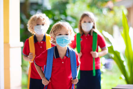 Photo for School child wearing face mask during corona virus and flu outbreak. Boy and girl going back to school after covid-19 quarantine and lockdown. Group of kids in masks for coronavirus prevention. - Royalty Free Image