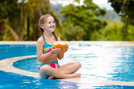 Photo pour Child with coconut drink in outdoor swimming pool. Kids swim in tropical resort. Healthy exotic fruit refreshment for children. Travel with young kid. Beach and water fun. Summer family vacation. - image libre de droit