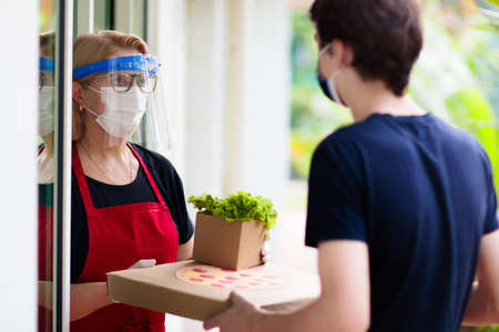 Photo for Food delivery in lockdown. Take away food during coronavirus outbreak. Restaurant owner in face mask holding pizza and salad box. Stay home and be safe. Meal order in covid-19 pandemic. - Royalty Free Image