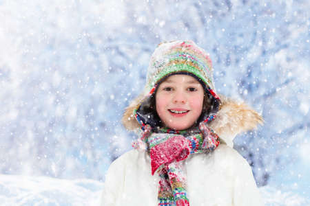 Photo for Child playing with snow in winter. Little boy in colorful jacket and knitted hat catching snowflakes in winter park on Christmas. Kids play and jump in snowy forest. Snow ball fight for children. - Royalty Free Image