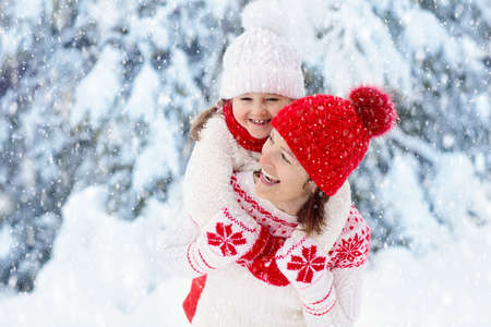Photo for Mother and child in knitted winter hats play in snow on family Christmas vacation. Handmade wool hat and scarf for mom and kid. Knitting for kids. Knit outerwear. Woman and little girl in snowy park. - Royalty Free Image