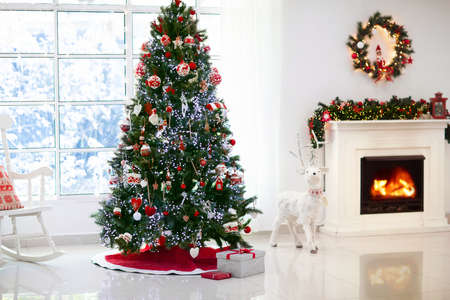 Photo pour Decorated room with Christmas tree and fireplace. Xmas presents and gifts on holiday eve. Lights, fir garland with baubles and ornaments and reindeer figure. Family home decoration. - image libre de droit