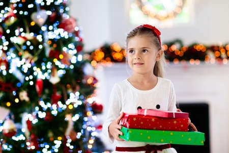 Photo pour Family on Christmas morning at fireplace. Kids opening Xmas presents. Children under Christmas tree with gift boxes. Decorated living room with traditional fire place. Cozy warm winter day at home. - image libre de droit