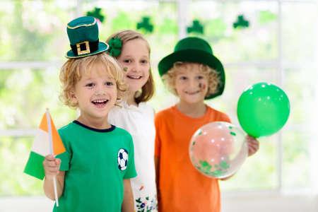 Photo pour Family celebrating St. Patrick's Day. Irish holiday, culture and tradition. Kids wear green leprechaun hat and beard with Ireland flag and clover leaf. Children having fun at St Patrick party. - image libre de droit