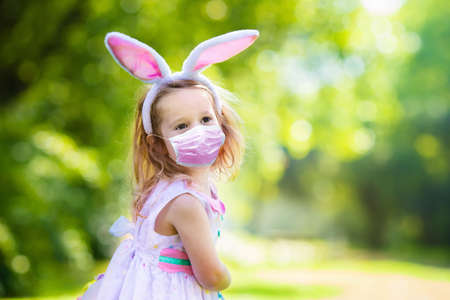 Photo pour Little girl in face mask having fun on Easter egg hunt in outbreak. Kids in bunny ears and rabbit costume in pandemic celebration. Children with colorful eggs. Safe celebration. - image libre de droit