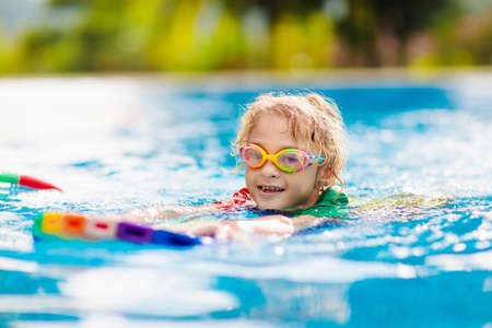 Photo pour Child learning to swim in outdoor pool of tropical resort. Kids learn swimming. Exercise and training for young children. Little boy with colorful float board in sport club. Swimming baby or toddler. - image libre de droit