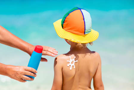 Photo pour Mom applying sunscreen on child. Safe beach and sun tan fun. UV protection for young kid. Skin health care. Sun block spf cream and lotion for kids. Summer vacation with children. - image libre de droit