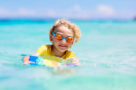 Photo pour Child surfing on tropical beach. Family summer vacation in Asia. Kids swim in ocean water. Kid on surf body board. Little boy swimming in exotic sea. Travel with children. Water and beach sport. - image libre de droit