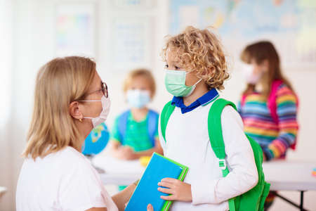Photo pour Teacher in class, school child in face mask during virus and flu outbreak. Boy and girl back to school after quarantine and lockdown. Group of kids in masks for virus prevention. - image libre de droit