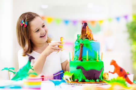 Photo for Kids birthday party. Dinosaur theme cake. Little girl blowing candles and opening gifts. Children event. Decoration for dinosaurs themed celebration. - Royalty Free Image
