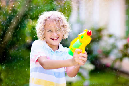 Photo for Kids play with water gun toy in garden. Outdoor summer fun. Little boy playing with water hose in sunny backyard. Party game for children. Healthy activity for hot sunny day. - Royalty Free Image