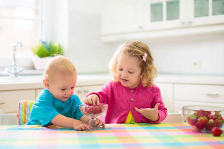 Photo pour Child having breakfast. Kid drinking milk and eating cereal with fruit. Little boy and girl at white dining table in kitchen at window. Kids eat on sunny morning. Healthy balanced nutrition for kids. - image libre de droit