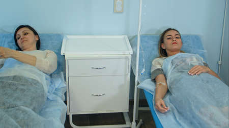 Two female patients on drips lying on beds in hospital ward being checked by male doctor