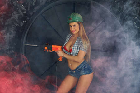 Photo pour girl in construction clothes and protective equipment posing  on grunge background - image libre de droit