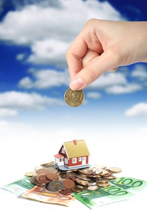 Invest in real estate concept. House money and hand.